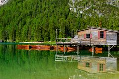 Wooden lake house at Lake Braies also known as Pragser Wildsee  in beautiful mountain scenery. Amazing Travel destination Lago di stock image