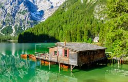 Wooden lake house at Lake Braies also known as Pragser Wildsee  in beautiful mountain scenery. Amazing Travel destination Lago di royalty free stock photography