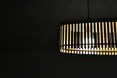 Wooden lamp. Wooden ceiling lamp lighted in the dark Stock Photo