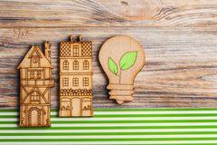 Wooden lamp and houses on green stripes background Royalty Free Stock Photo