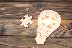 Wooden lamp from puzzles on a wooden background. Business idea. creation Royalty Free Stock Image