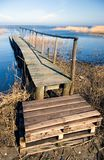 Wooden landing jetty. A weathered wooden landing jetty on a blue lake with reed beds Royalty Free Stock Images
