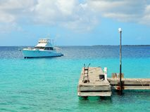 Wooden landing stage on Bonaire in the Caribbean with a motorboat in the back Stock Photo