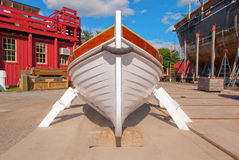 Wooden Lapstrake Workboat. Restored and repainted wooden workboat in boatyard.  Low angle perspective of the bow at midday, bright sun directly overhead. Light Stock Image