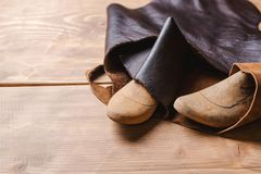 Wooden last for a kids shoe and piece of leather in a workshop. Stock Photography