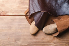 Wooden last for a kids shoe and piece of leather in a workshop. Stock Image