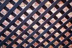 Wooden lattice. With a brick wall background stock photography