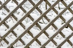 Wooden lattice made of larch planks after snowfall royalty free stock photography