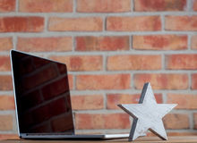 Wooden leader star and laptop Stock Photography