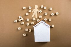 Wooden letter cubes   and man figurine and house. Wooden letter cubes   and man figurine and model house Stock Photo