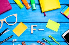 A wooden letter of grade F minus the student`s desk. School supplies on a blue wooden table. The concept of higher school stock photo