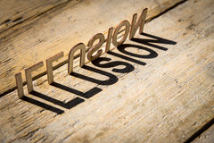 Wooden letters build the word illusion. Wooden letters on old aged wooden table build the shadow word illusion, vintage style stock image