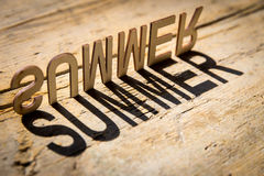 Wooden letters build the word summer. Wooden letters on old aged wooden table build the shadow word summer, vintage style royalty free stock photo