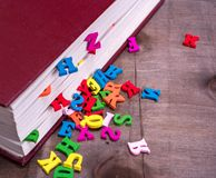 Wooden letters fall out of a closed book. Colored wooden letters fall out of a closed book in a red cover Stock Image