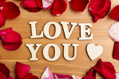 Wooden letters forming phrase Love You with rose petal besides Stock Images