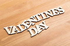Wooden letters forming phrase Valentines day over wooden backgro Royalty Free Stock Photos