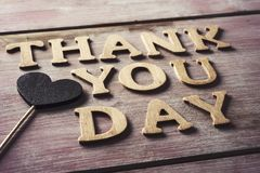 Wooden letters forming the text thank you day. Some wooden letters forming the text thank you day and a heart attached to a stick on a rustic wooden surface Stock Photo
