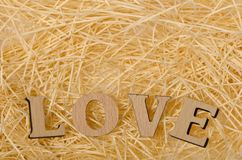Letters forming word LOVE. Wooden letters forming word LOVE on shredded paper texture Stock Photo