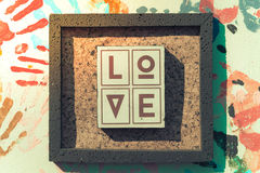 Wooden letters forming word LOVE written on wooden background. Stock Photos