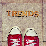 Wooden letters forming the word trends and the feet of a young m Royalty Free Stock Photo