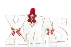 Wooden letters forming word XMAS with ribbons and red figures be Stock Images