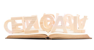 Wooden letters over the book's surface. Multiple wooden letters over the opened book's surface, composition isolated over the white background Stock Photos