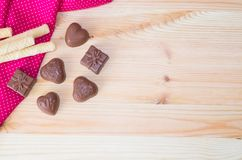 Wooden light background chocolate candy heart and a gift wafer tubules. Moth polish cloth Stock Images