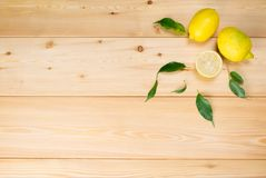 wooden light background with yellow lemons and green leaves stock image