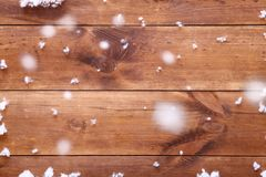 Wooden brown background table with white snowflakes, empty blank wood board and falling snow, top view, copy space. Wooden light brown background table with Stock Images