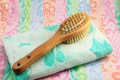 Wooden brush with the handle for massage of a body and a towel. Stock Photography