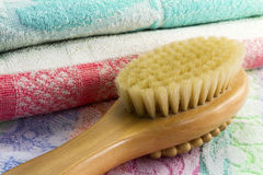Wooden brush with the handle for massage of a body and a towel. Royalty Free Stock Photos