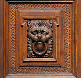 Wooden lion cub holding a door handle in his mouth Stock Images