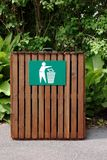 Wooden Litter Bin. Wooden slatted litter bin with sign in white and green. Mixed green fauna to the rear Stock Image