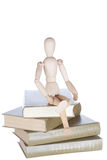 Wooden little man sits on books Stock Photo