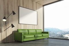 Wooden living room, green sofa, poster. Minimalist living room interior with a wooden wall, a concrete floor, a green sofa and a bench. A panoramic window and a Stock Photography