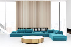 Wooden living room interior, blue sofas. White and wooden living room interior with a round table, blue sofas and armchairs near it, tall windows and book Stock Photo