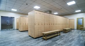Wooden lockers with a wood bench in a locker room. With doors closed. Locker room interior in modern fitness gym royalty free stock image