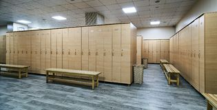 Wooden lockers with a wood bench in a locker room. With doors closed. Locker room interior in modern fitness gym royalty free stock photography
