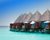 Wooden lodges on a beach at water Stock Photo