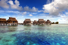 Wooden lodges on piles stand in an island lagoon against the cloudy sky Royalty Free Stock Photo