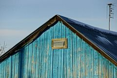 A wooden loft with a small blue window Royalty Free Stock Photos