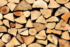 Wooden log texture background with different type and sizes of logs for firewood put on one large pile. On warm sunny day stock photo