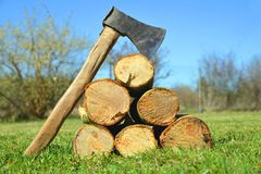 Wooden logs with old axe. Stock Photo