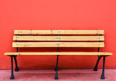 Wooden long bench against blank red wall. On background Royalty Free Stock Photography