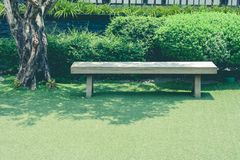 Wooden long bench stand on green grass meadow field of outdoor garden in Japanese style at public park. Selective focus royalty free stock photography