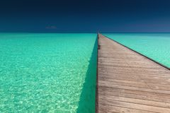 Wooden long jetty over lagoon with amazing clean azure water. Maldives Royalty Free Stock Photos
