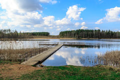 Wooden Long Pier in the Lake. View of wooden pier inside lake, scenic view of reflection of the clouds and trees on lake, with cloudy blue sky background royalty free stock photo