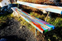 Wooden long white bench. Painted in stripes of colored streaks. Place in the viewpoint. Risor, Aust-Agder region of Ostlandet. Eastern Norway stock photo
