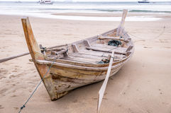 Wooden longtail boat on beach in Ko Lanta, Thailand. Wooden longtail boat sitting on Ao Kantiang beach at low tide in Ko Lanta, Thailand Royalty Free Stock Image