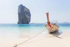 Wooden longtail boat mooring on the tropical beach with limestone rock symbol of Poda island  krabi Thailand Royalty Free Stock Photo
